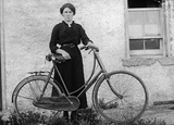 Unknown woman standing leaning against a bike